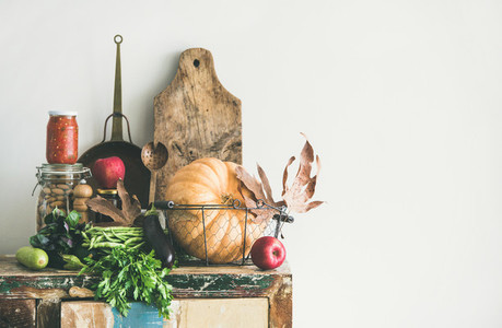 Autumn food ingredients and utensils over wooden cupboard copy space