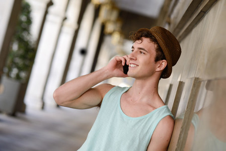 Attractive young man wearing hat talking on the mobile phone