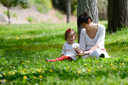 Mother and little girl playing in the park
