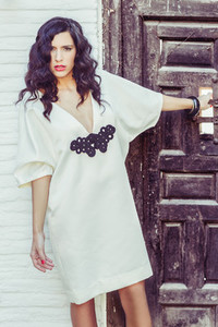 Woman model of fashion wearing white dress with curly hair