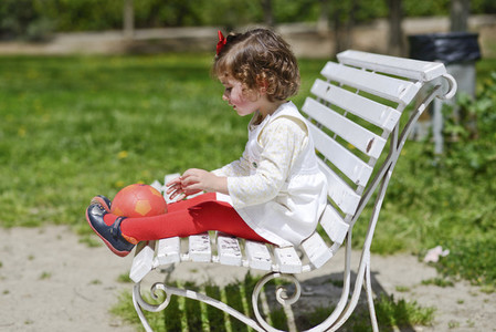 Little girl playing with a ball sitting on a park bench