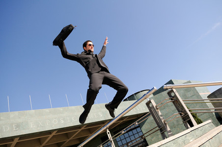 Businessman jumping in the street