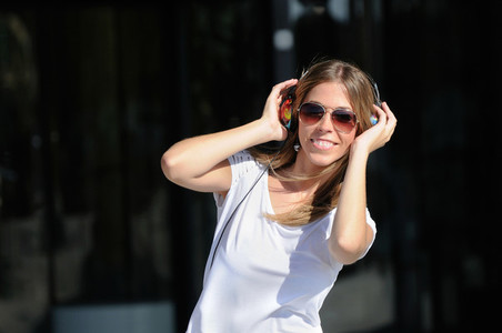 Young girl with headphones in the street