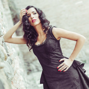 Woman  model of fashion  wearing black dress with curly hair