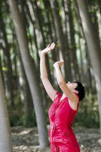 Woman dressed in red  meditating in the forest