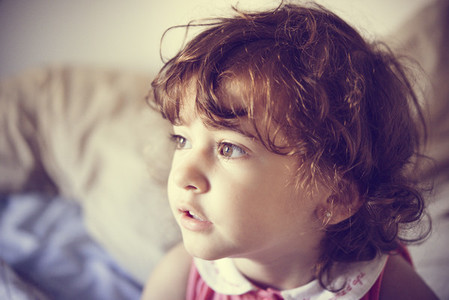 Adorable little girl with curly hair tousled