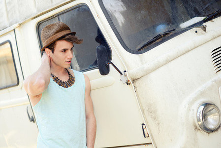 Young handsome man with an old van wearing sun hat
