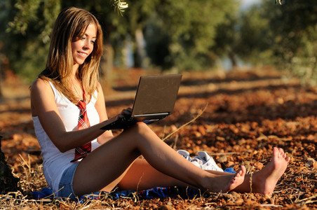 Girl with a laptop in a field in autumn