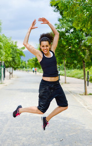 Young cheerful smiling woman in sports wear in urban background
