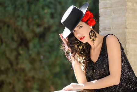 Woman wearing spanish hat and red carnations in her hair