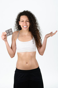 Beautiful young mixed woman eating a chocolat tablet isolated o