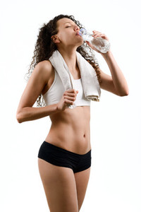 Young woman wearing sport clothes and drinking water on white ba