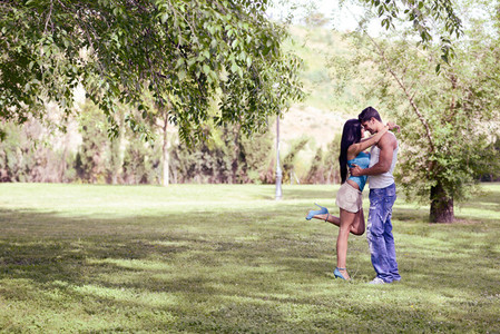 Young couple kissing in a beautiful park