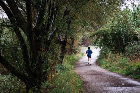 Woman runner running in autumn forest