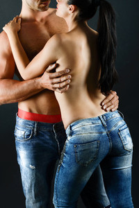 Sexy young couple with blue jeans standing together