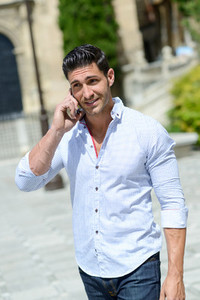 Handsome man in urban background talking on phone