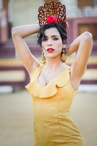Woman model of fashion wearing a dress in a bullring