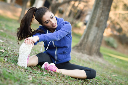 Happy young woman stretching before running outdoors