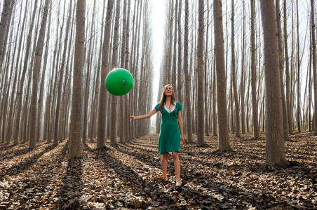 Beautiful blonde girl  dressed in green  walking into the forest