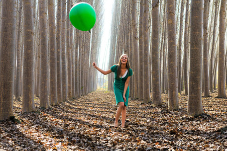 Beautiful blonde girl  dressed in green  laughing in the forest