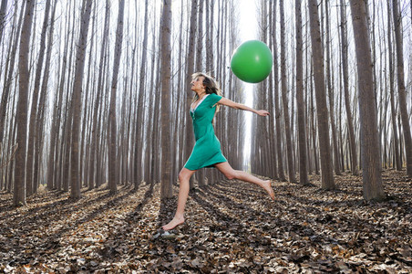 Beautiful blonde girl  dressed in green  jumping into the woods