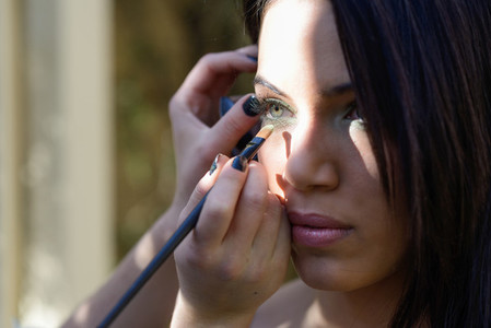 Make up applying eyeshadow on models eye