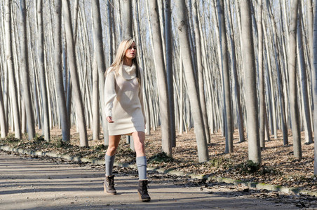 Beautiful blonde girl  dressed with beige dress  walking in a ru