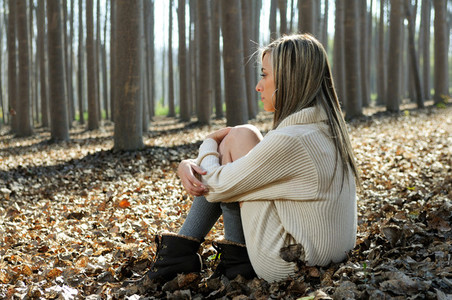 Beautiful blonde sitting on leaves in a forest of poplars