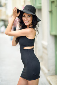 Brunette woman wearing black seductive dress in the street
