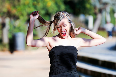 Beautiful and fashion girl with pigtails shouting and dancing