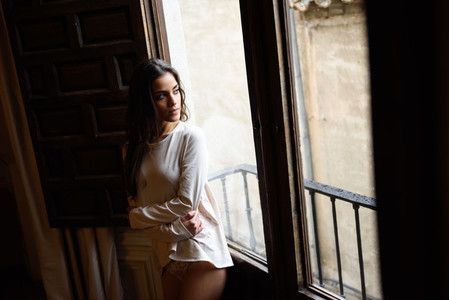 Woman in pyjama and white panties posing near a window