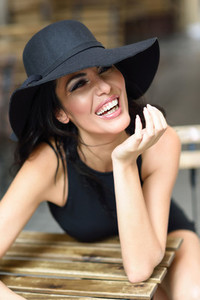 Woman wearing black seductive dress sitting in a outdoors bar