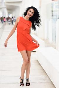 Brunette woman wearing orange short dress in a harbor