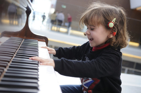 little girl having fun playing the piano