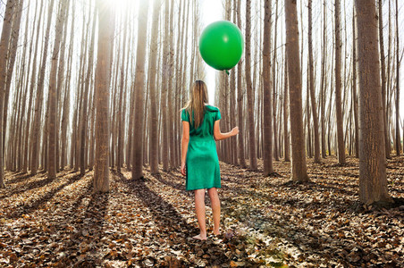 Beautiful blonde girl dressed in green standing in the forest