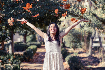 Beautiful brunette girl with falling leaves in the autumn