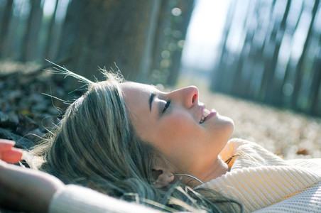 Smiling blonde girl lying on leaves in a forest of poplars