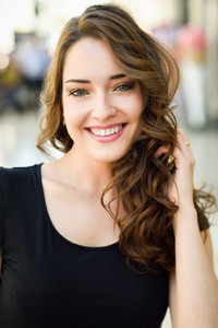 Beautiful young woman with blue eyes smiling in urban background