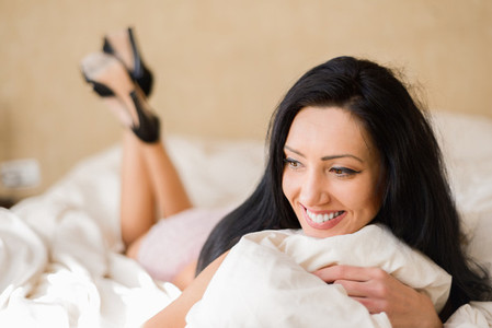 Woman in lingerie lying on the bed in her bedroom