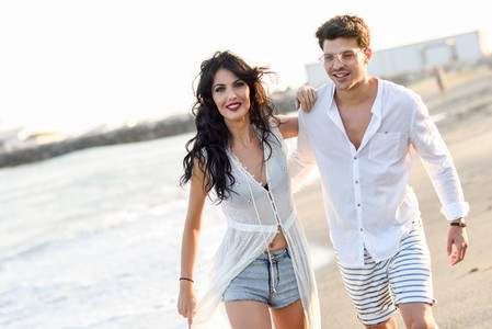 Young happy couple walking in a beautiful beach