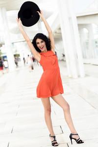 Brunette woman wearing orange seductive dress in the street