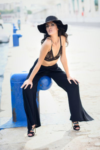 Brunette woman wearing black bra and trousers