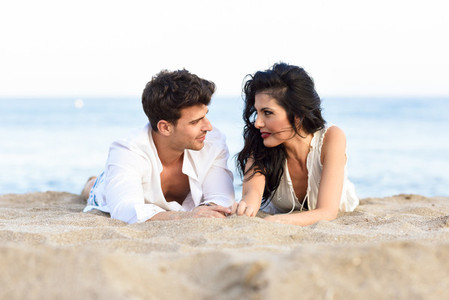 Young happy couple lying on the sand in a beautiful beach