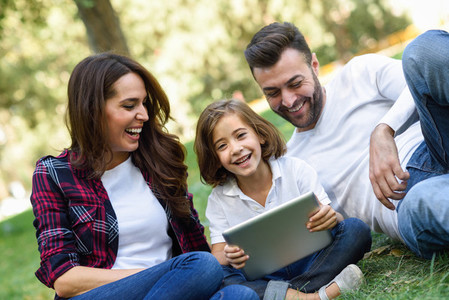 Happy family in a urban park playing with tablet computer