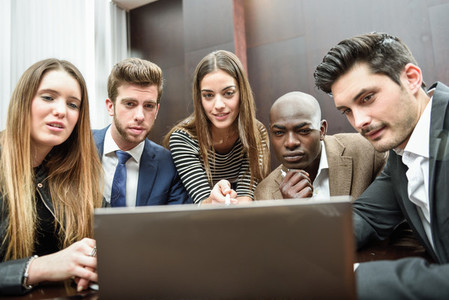 Group of multiethnic busy people looking at a laptop