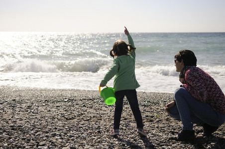 Mother and little girl having fun on the beach in winter