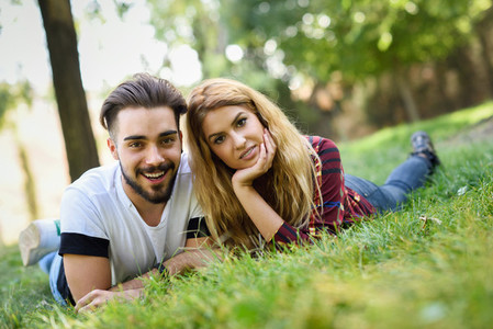 Beautiful young couple laying on grass in an urban park