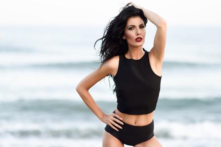 Brunette woman wearing black top and panties near a beach