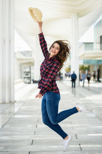Girl with beautiful blue eyes in jumping in urban background