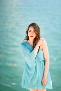 Woman with blue eyes wearing blue dress in the beach
